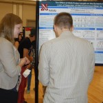 Savannah explaining her summer research project  to Neal Bryan at UNL Graduate Studies.
